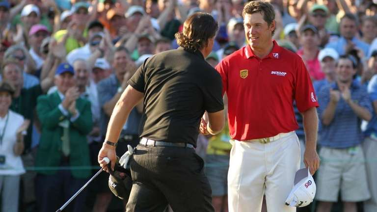 Phil Mickelson (L) shakes hands with Lee Westwood