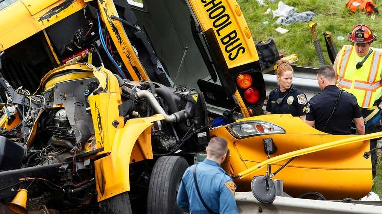 Emergency personnel examine a school bus after it