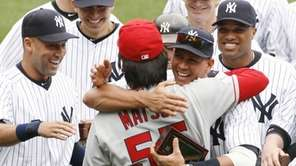 Los Angeles Angels' Hideki Matsui, center, is embraced