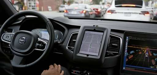 An Uber driverless car waits in traffic during