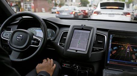 An Uber driverless car waits in traffic during