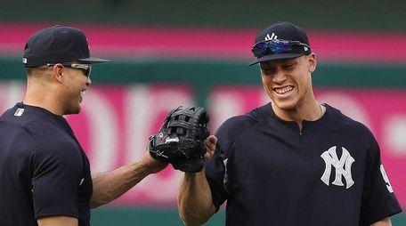 Yankees' Giancarlo Stanton, left, jokes with teammate Aaron