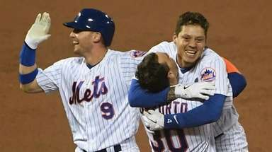 The Mets' Wilmer Flores celebrates his walk-off sacrifice