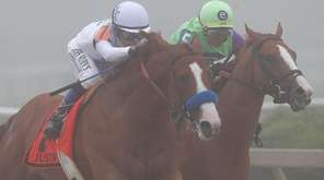 Justify, left, ridden by jockey Mike Smith, leads