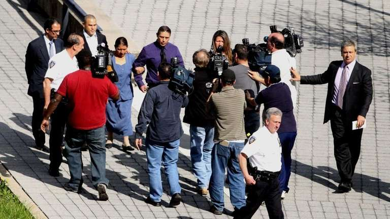 A scrum of photographers precedes the arrival of