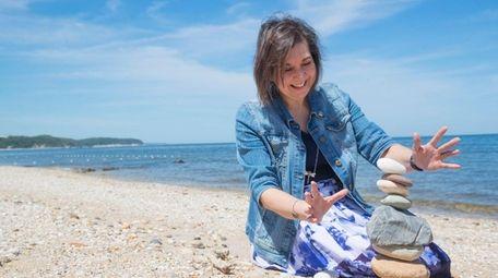 Susan Brinkman, of Patchogue, builds a cairn sculpture