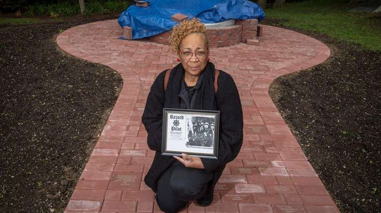 Sheryl Goodine, widow of Jerome Goodine Sr., hold