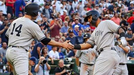 The Yankees' Neil Walker, left, greets Gleyber Torres