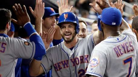 Mets catcher Kevin Plawecki is congratulated after scoring
