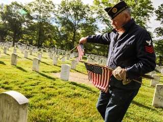 Navy veteran Tom Taylor of Farmingdale places flags