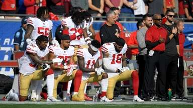 Members of the San Francisco 49ers kneel during