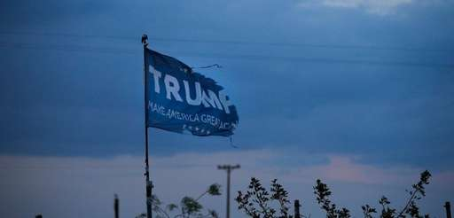 A withered Donald Trump campaign flag stands on
