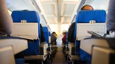 Travelers inside an airplane preparing for takeoff.