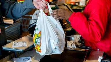 A cashier hands a shopper a plastic bag
