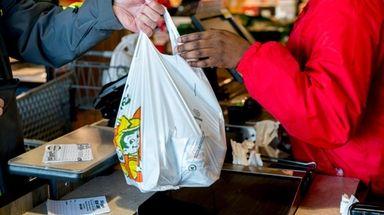 A cashier hands a shopper a plastic bag