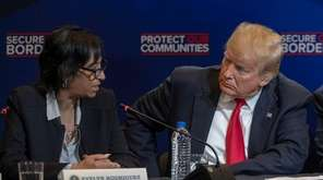 President Donald Trump listens as Evelyn Rodriguez talks