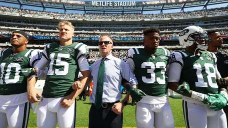 Jets chairman Christopher Johnson stands in unison with