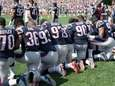 Patriots players hold hands and kneel during the