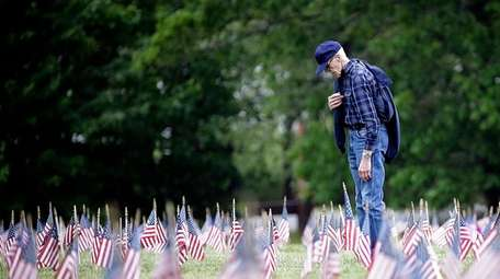 A man says a prayer during the Memorial
