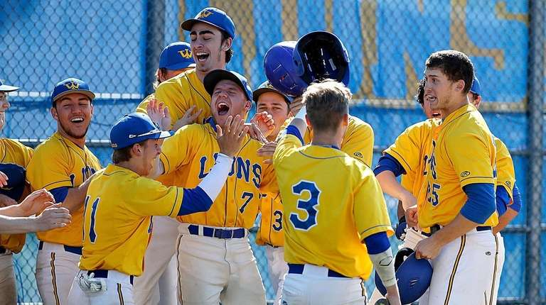 The West Islip bench cheers Tommy Parson (25)
