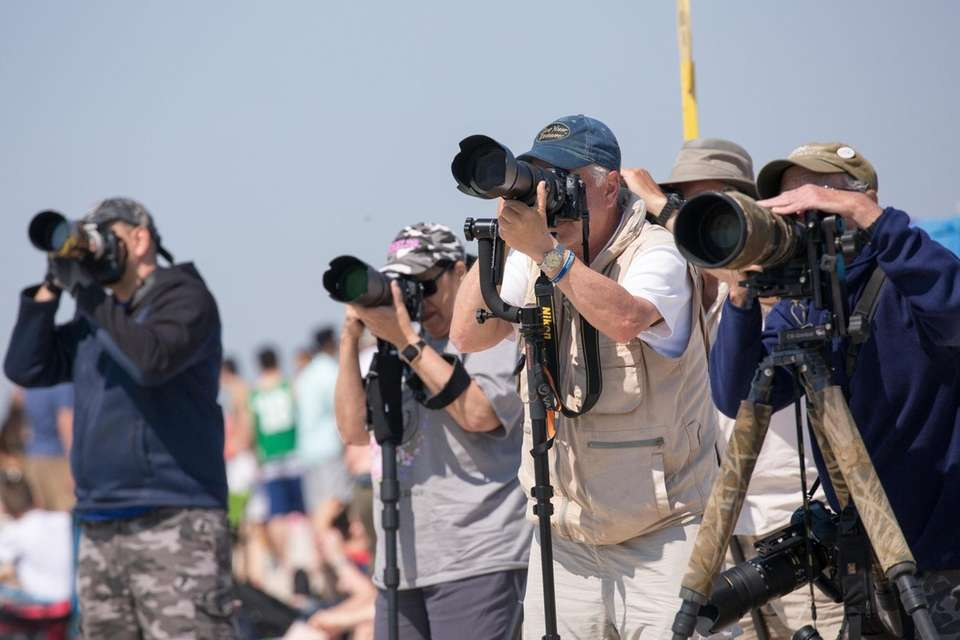 Photographers train their cameras skyward during a rehearsal