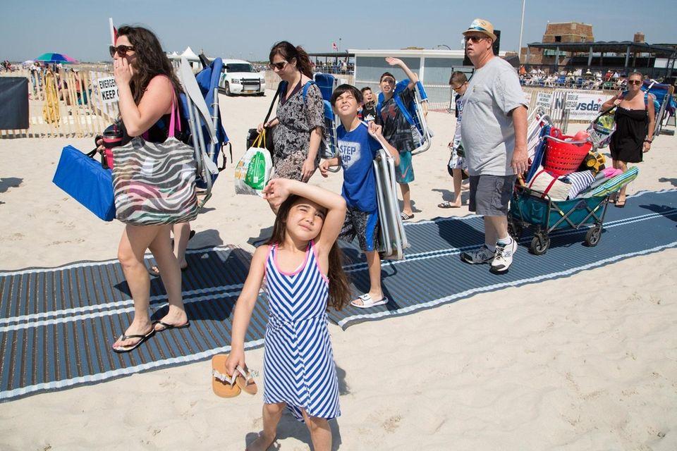 Beachgoers look skyward as they arrive for a