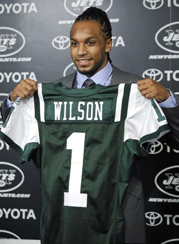 Kyle Wilson holds up a Jets jersey after