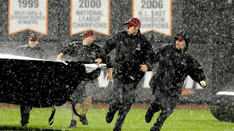 Grounds crews scramble to cover the field as