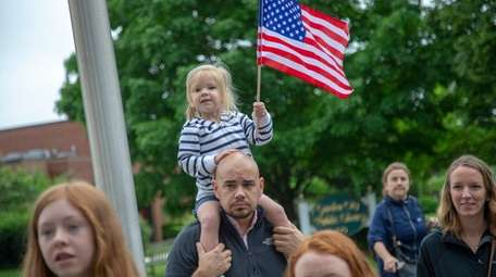 Charlotte Erb, 3, of West Hempstead, cheers on