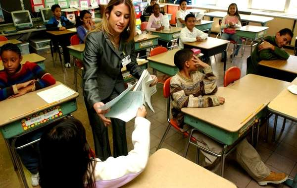 A teacher collects exams at Laurel Park Elementary