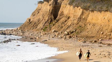 Surfers walk the beach near Camp Hero in