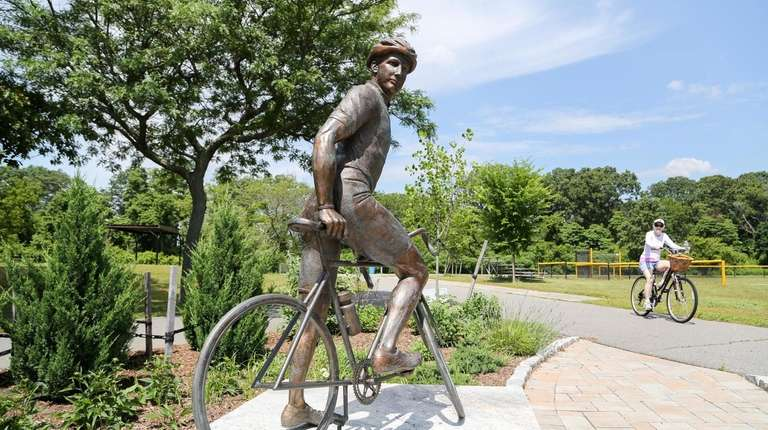 A cyclist rides past a statue of cyclist