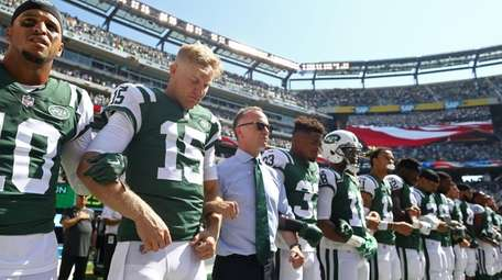 New York Jets chairman Christopher Johnson stands with