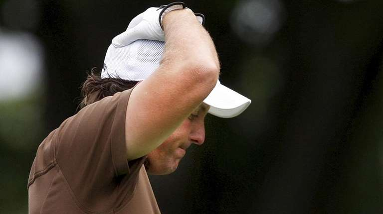 Phil Mickelson reacts to his tee shot on