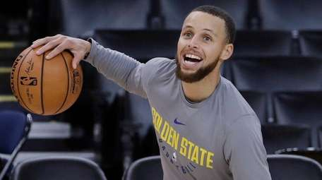 The Warriors' Stephen Curry smiles as he dribbles
