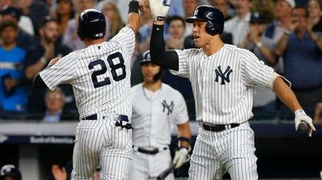 The Yankees' Austin Romine celebrates with Aaron Judge