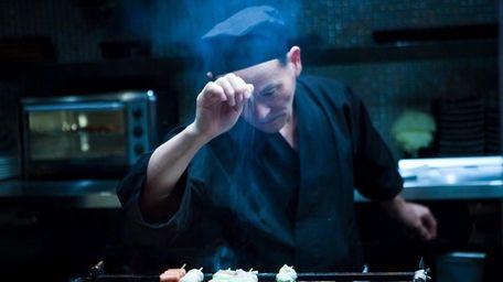 A yakatori chef seasons the meat as it