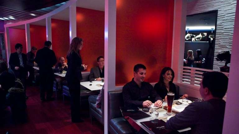 Patrons dine in modern red booths at Two