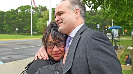 Linda Mangano, embraces her attorney John Carman, outside