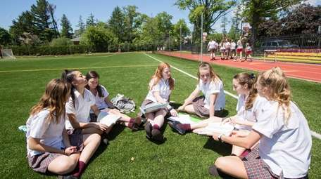 Students study together on an athletic field at