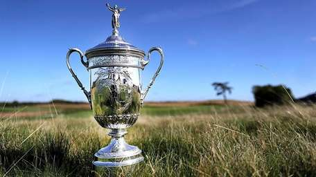The U.S. Open trophy in the fescue beside