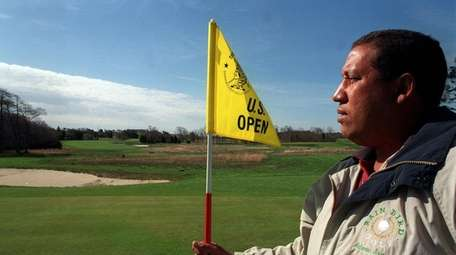 Greens superintendant Peter Smith holds the pin on