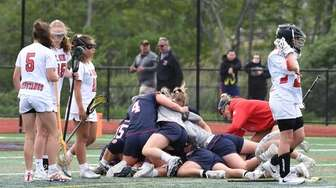 Cold Spring Harbor players celebrate their 13-12 overtime
