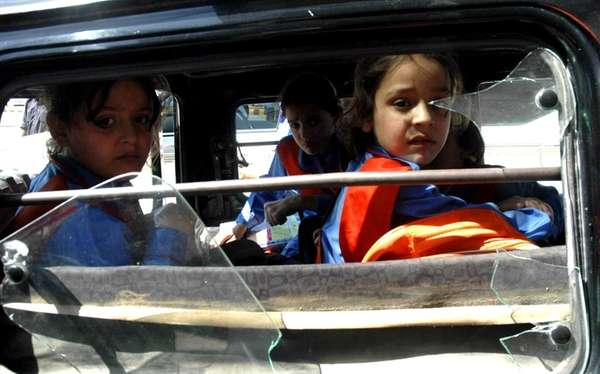 Pakistan students sit inside a vehicle after a
