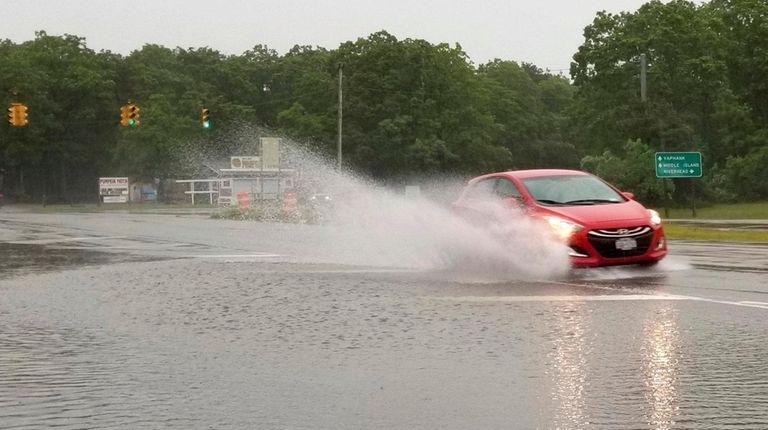 A car drives through a flooded County Road