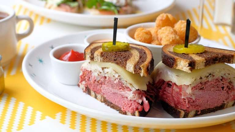 A Reuben sandwich stands tall topped with beer