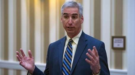 Oliver Luck speaks with members of the media