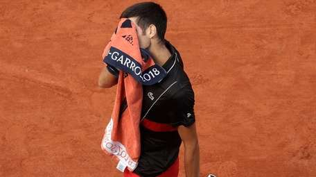 Novak Djokovic uses a towel in his French