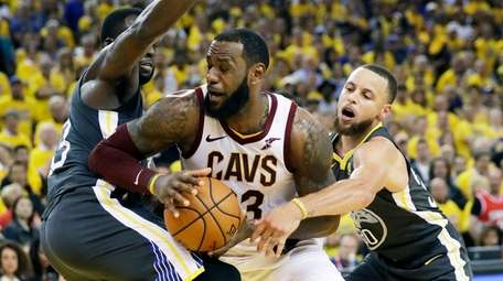 Cavaliers forward LeBron James, center, is defended by