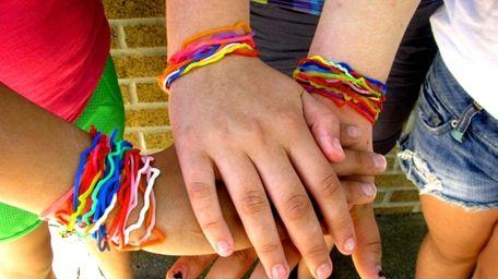 Three girls show off their Silly Bandz bracelets